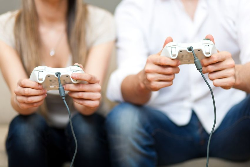Two people playing video games with white controllers