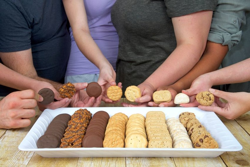 Group of people holding assortment of various Girl Scout cookies on a white tray
