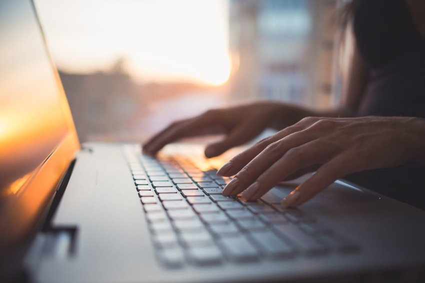 Up close view of person's hands typing at a laptop computer, reflecting the sunset