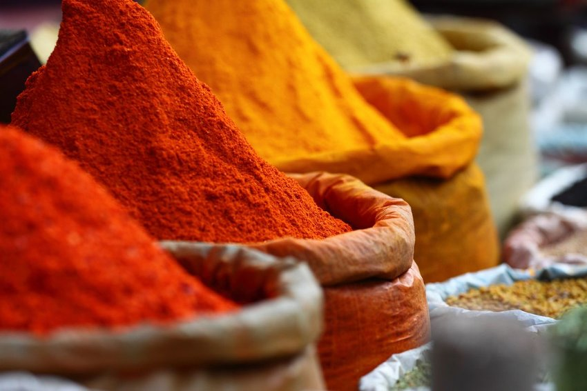 Various Indian spices in different hues of red, yellow, and orange sitting in street market