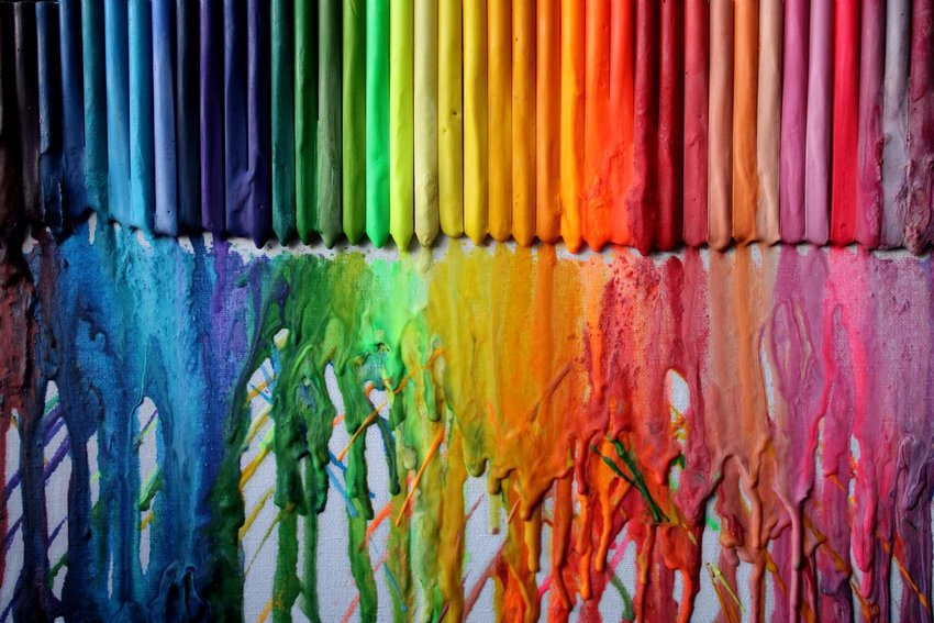 Multicolored pastels in rainbow hues melting and dripping down a stark white wall