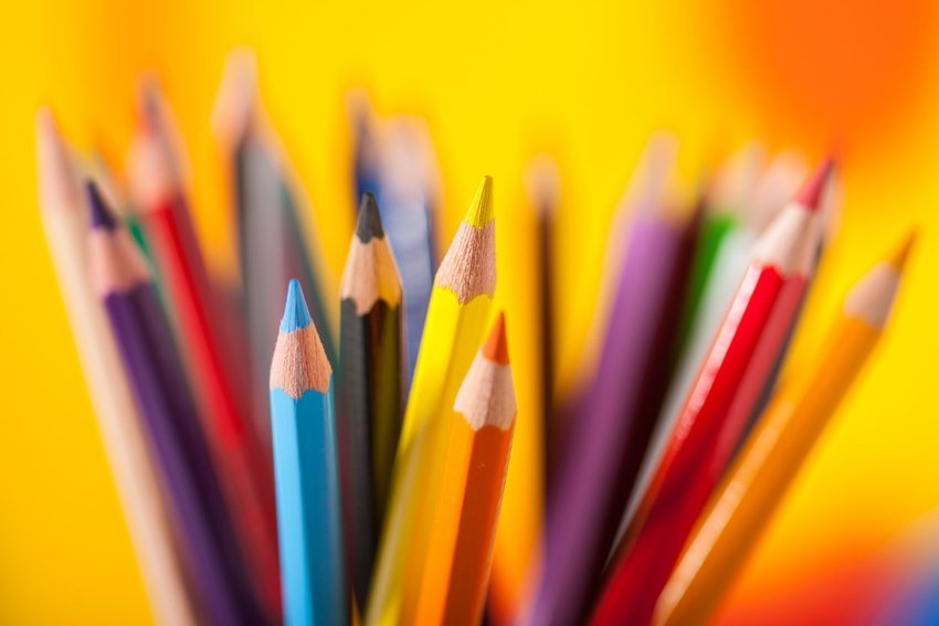 Pile of sharpened Crayola colored pencils against a bright yellow background
