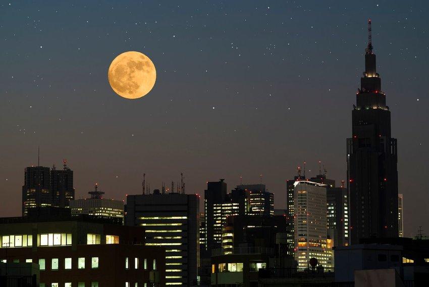Full moon rising over a city skyline