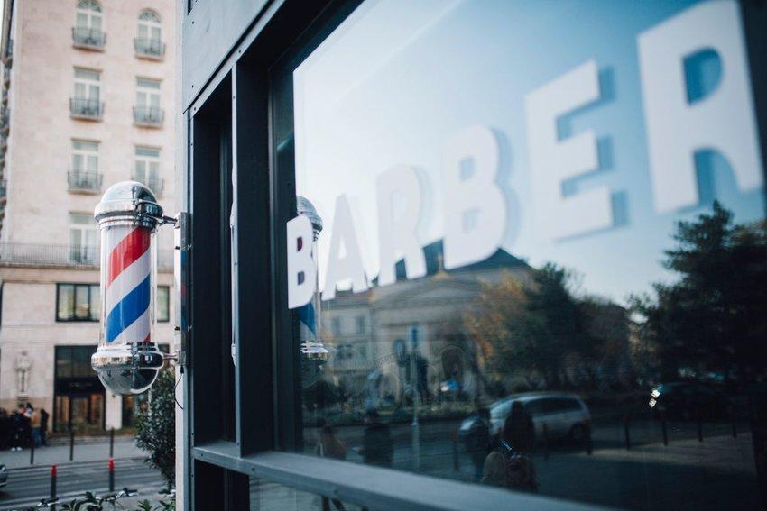 Barber shop window with barber shop striped pole on corner of shop