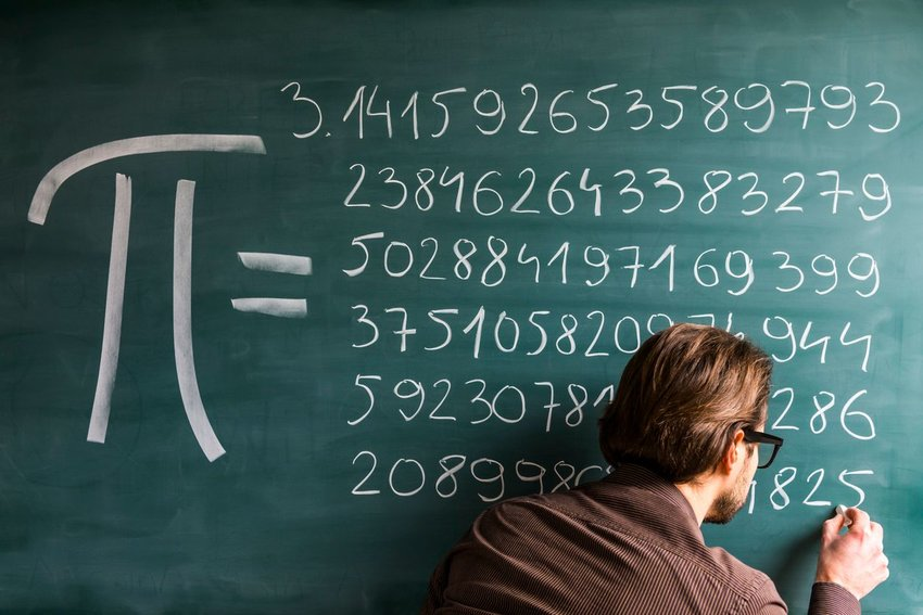 Person writing pi on a chalkboard