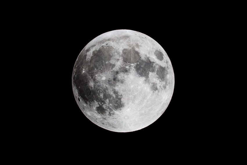 Close up of full moon in the pitch black sky