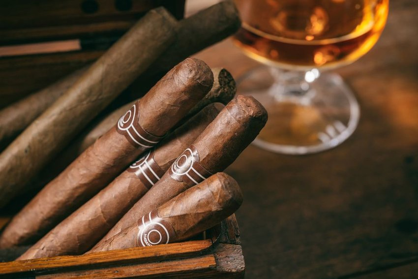 Wooden box of cigars with drink in background