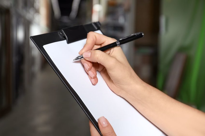 Person holding a clipboard and a pen