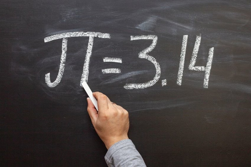 Person writing what pi is equal to on a chalkboard