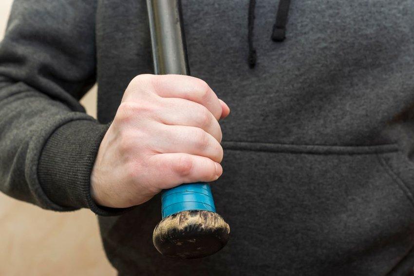 Man in gray sweatshirt holding brown wooden bat in right hand