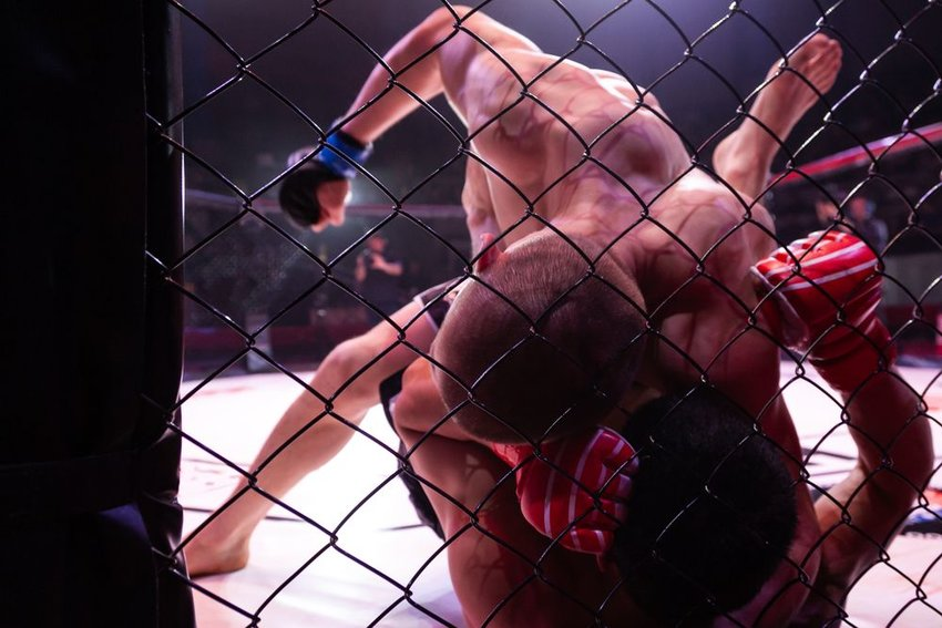 Two martial artists grapple and fight in close combat arena cage match