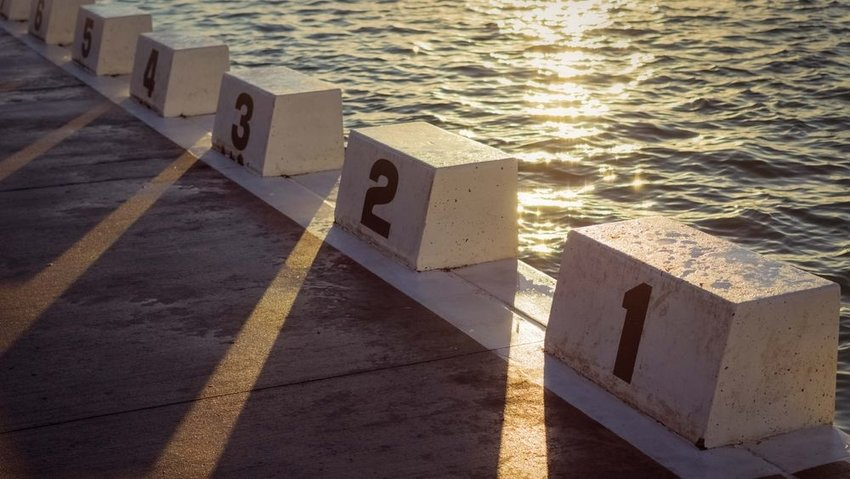 Swimming blocks rest on a pier beside large body of water, sun reflecting off waters surface