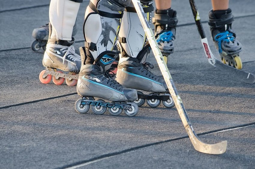 Up close view of roller hockey players, showing roller blades and hockey sticks