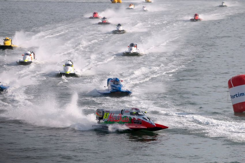 Group of motor boats race across waters, with huge foamy wakes and waves