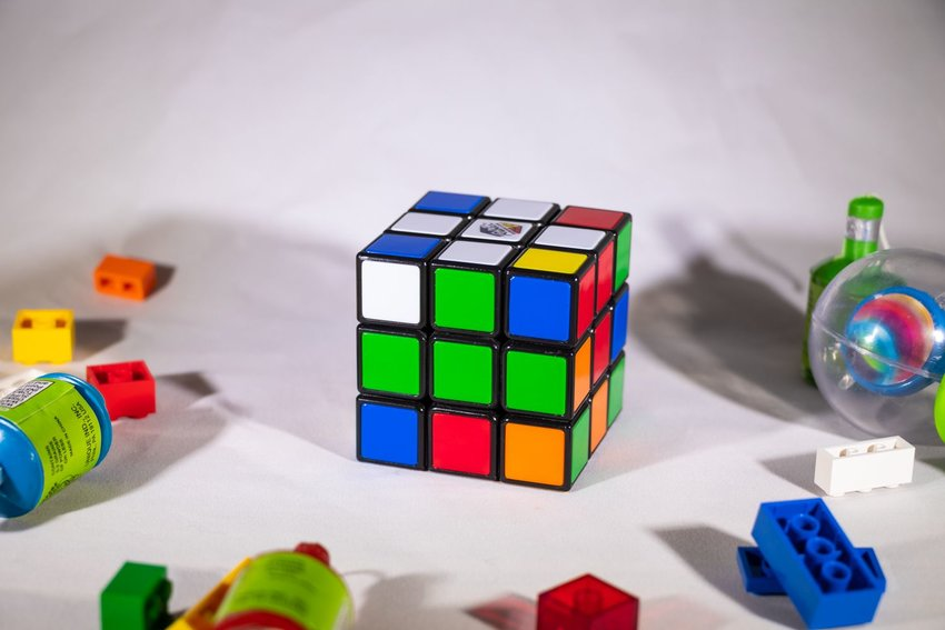 View of Rubik's Cube on white surface showing initial stage of progress completion