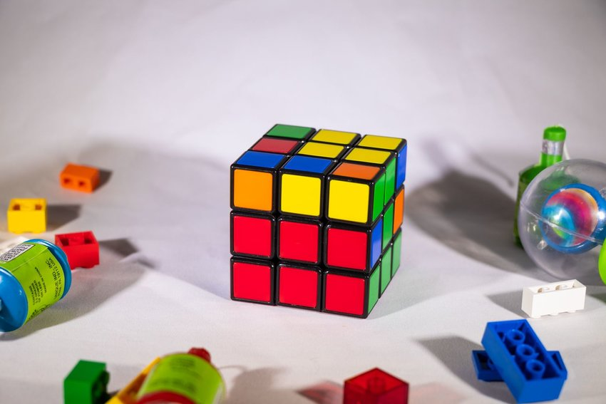 Up close view of Rubik's Cube showing partial completion on a cluttered white table