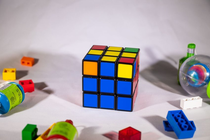 Rubik's Cube on white table nearing completion, surrounded by LEGO and toys