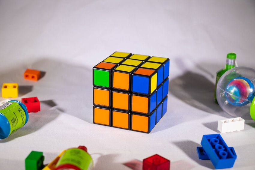 Rubik's Cube on a white table, showing orange, blue, and yellow squares nearing completion