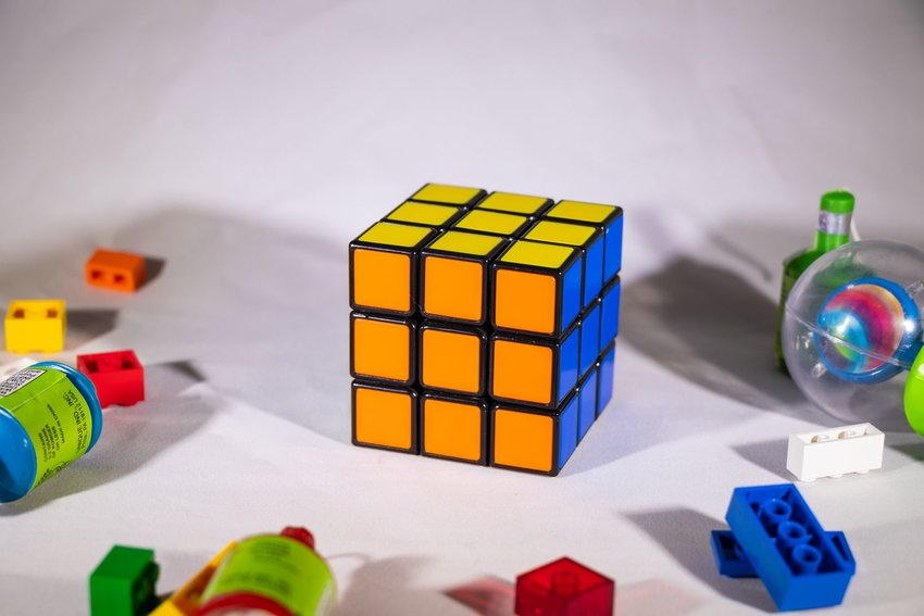Completed Rubik's Cube on a white table, surrounded by cluttered toys