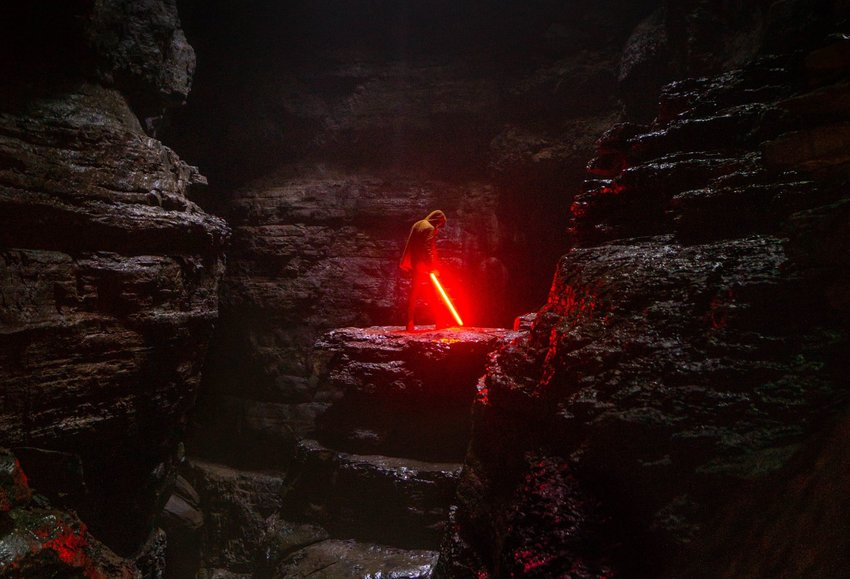 Person standing in rocky cave with red light