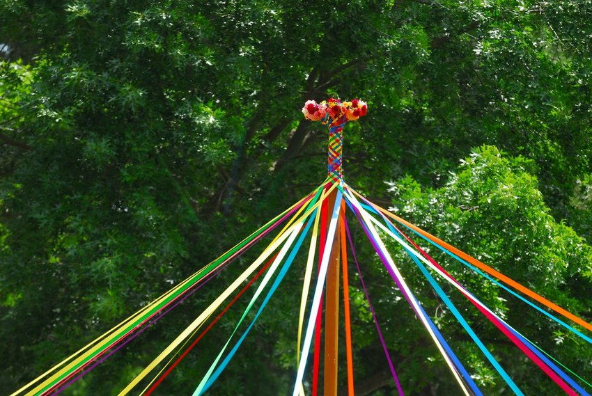 May Day pole celebration with different colored ribbons and flowers on top