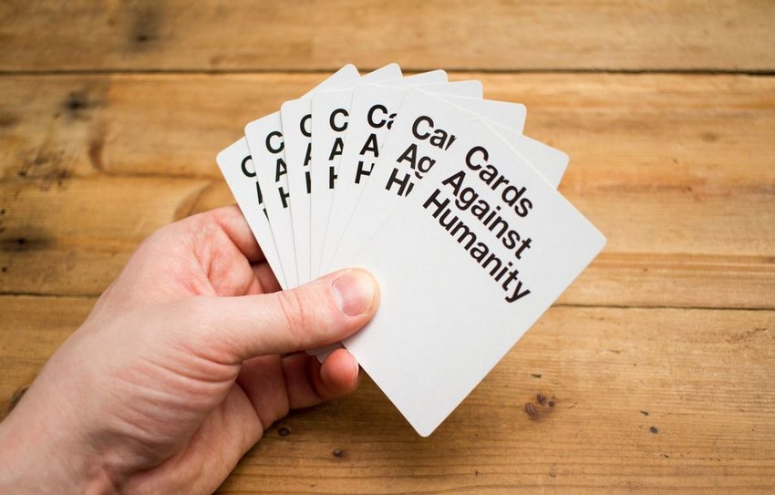 Person holding up cards against a wooden table