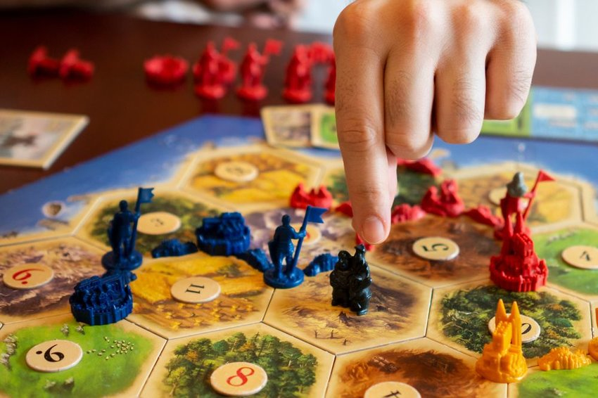 Person moving their game piece on a Catan board