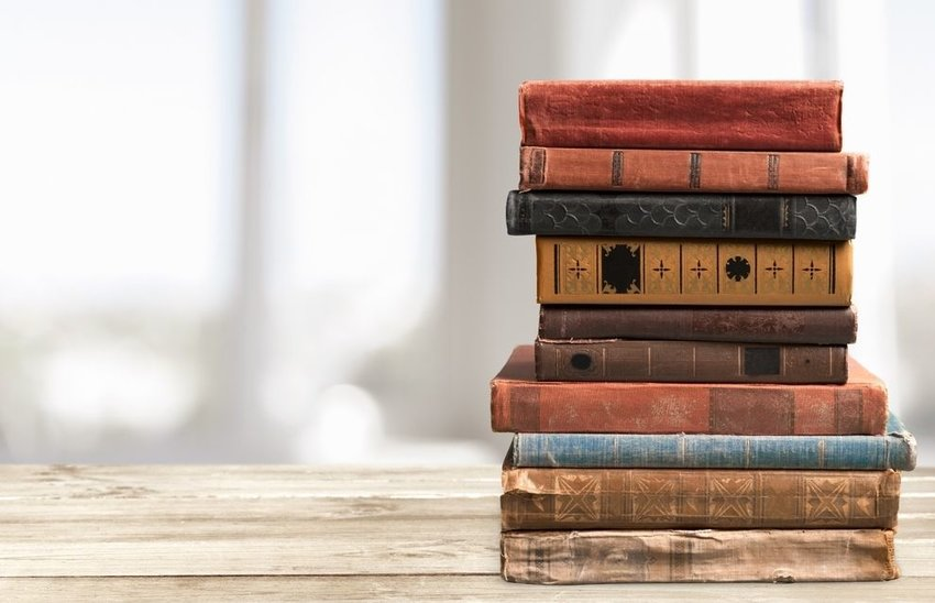 Stack of old books with different colored spines on a wooden table