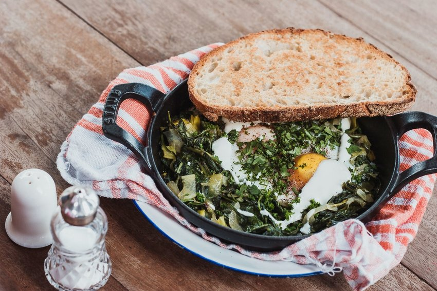Cast iron skillet with eggs and greens with toast resting on top