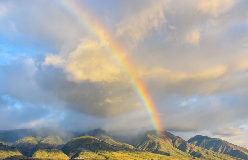 Rainbow over green mountains with clouds in Hawaii