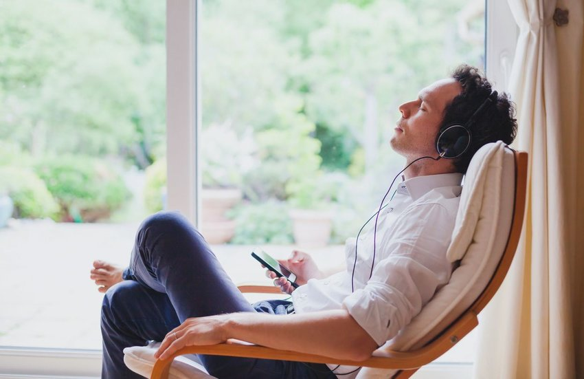 Man laying back in chair listening to music through headphones