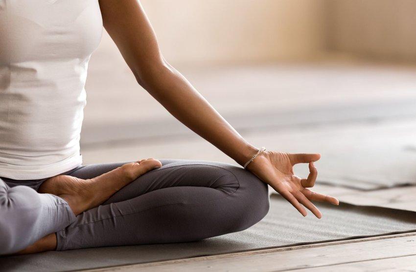 Person practicing meditation on a yoga matt