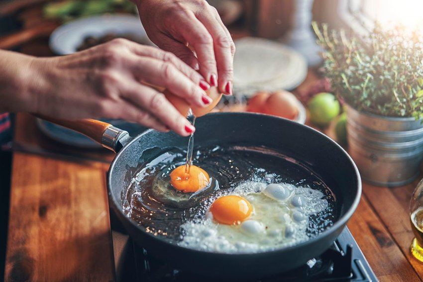 Person cooking eggs in a cast iron skillet