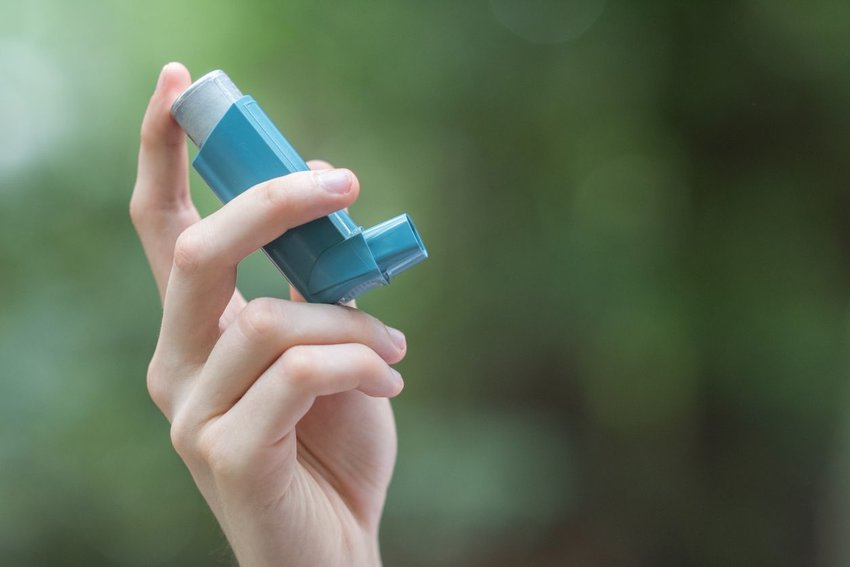 Person holding up a blue inhaler with background out of focus