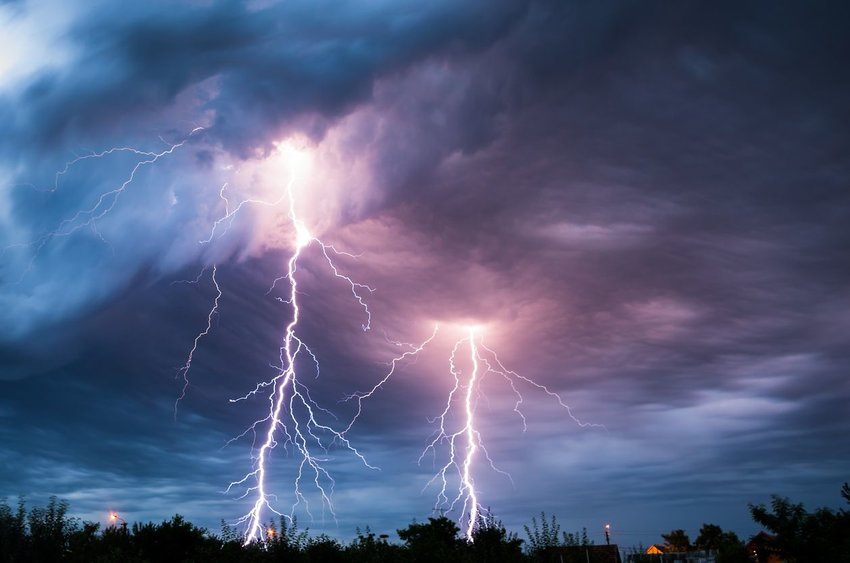 Strikes of lightning comes through purple and blue clouds