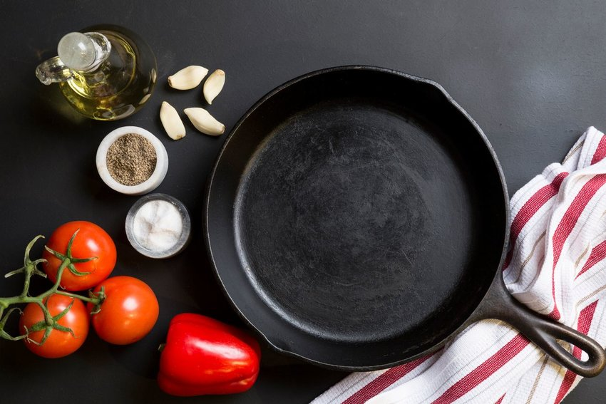 Cast iron skillet with oil, pepper, salt and vegetables on the side