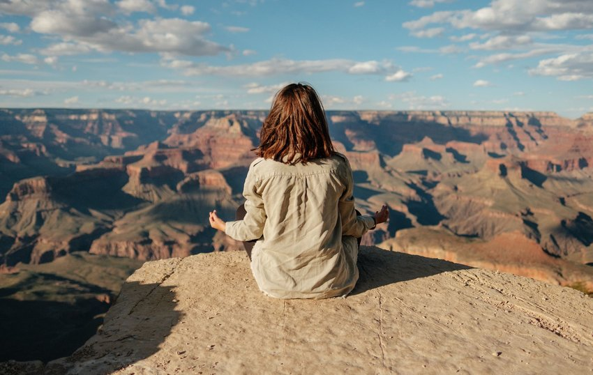 Person meditating on the ground with view of a canyon