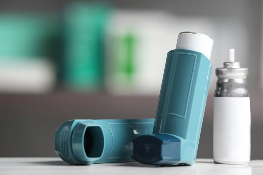 Two blue inhalers with refill sitting on a counter