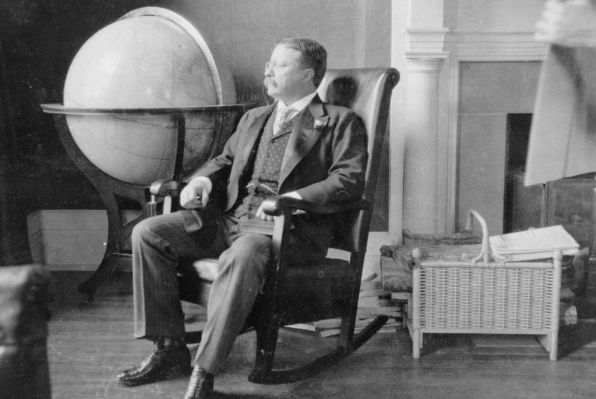 Theodore Roosevelt seated in rocking chair, by a large globe