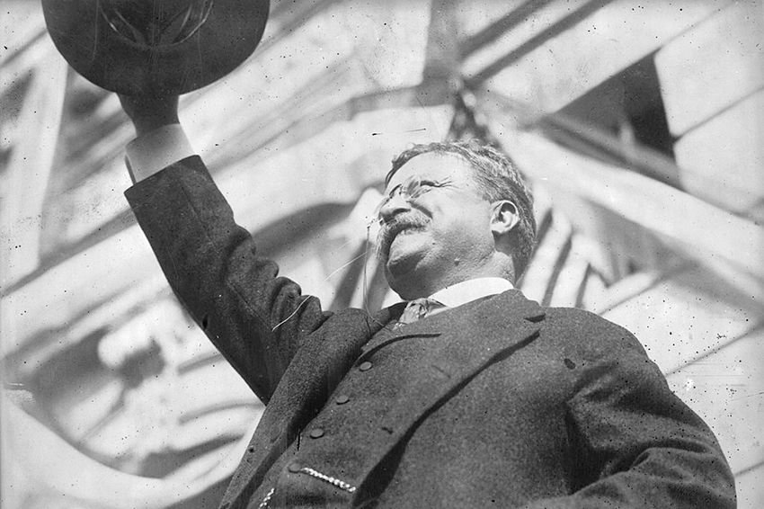 Theodore Roosevelt smiling with his hat in the air