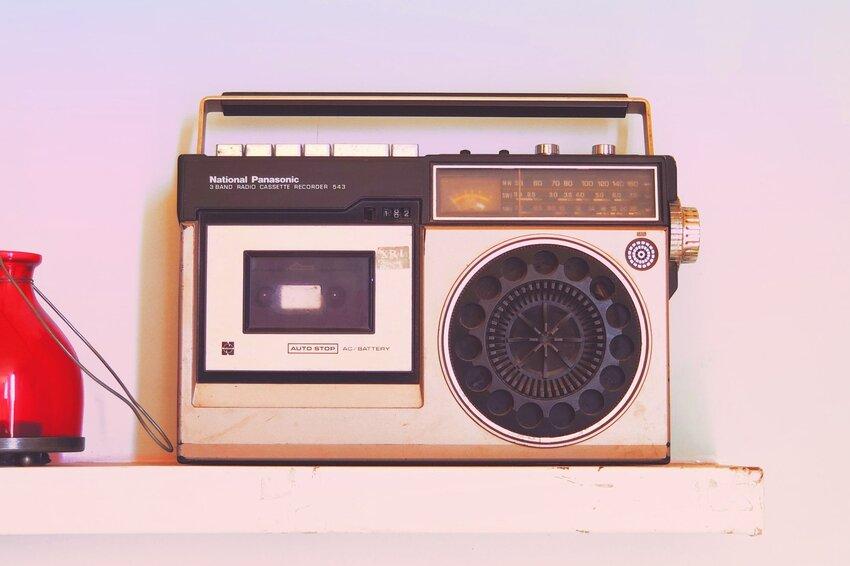 An old radio sitting on a white shelf