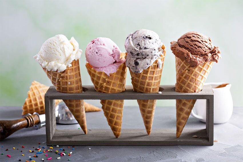 Several ice cream cones on a stand.