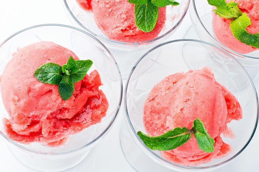 Top view of four glass dishes filled with strawberry sorbet and mint leaves.